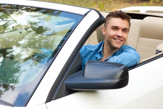 車にのってはにかむ男性