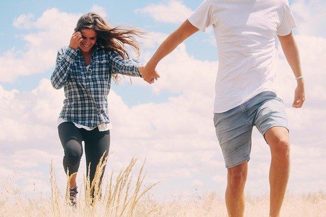 カップルが手を繋いで草原にいる画像