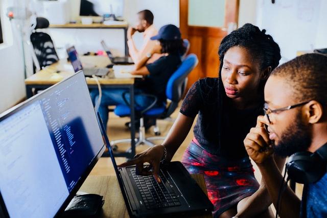 パソコンを前に会話する男女