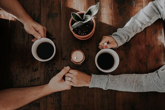 カフェで手を繋ぐカップル