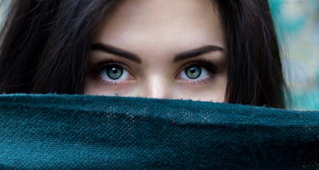 口を隠して目だけ出ている女性