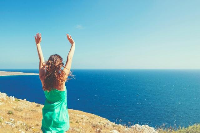 海を見ながら手をあげている女性