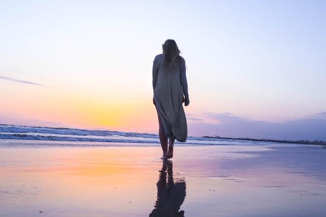 夕暮れのビーチを歩く女性