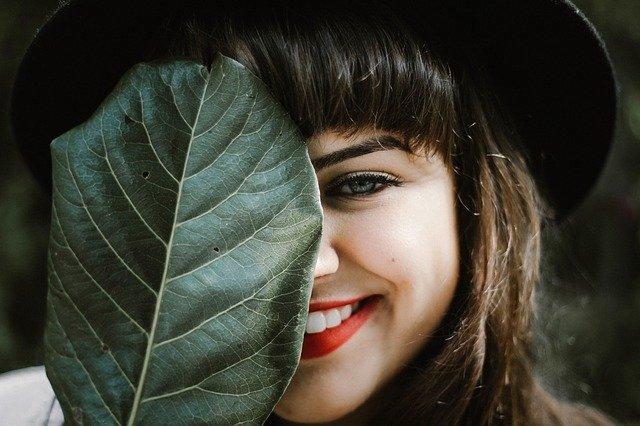 葉っぱで片目を隠しながら笑顔を見せる女性