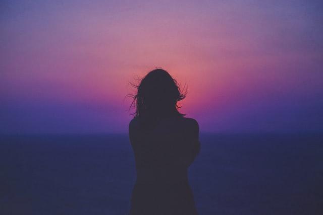 夕焼けに佇む寂しそうな女性