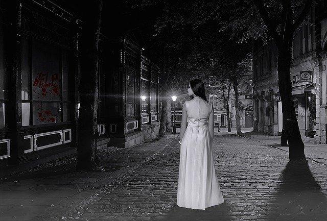 暗い道を歩く女性